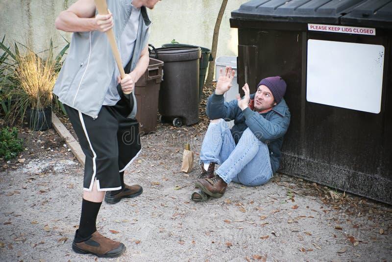 Задира угрожает бездомного человека стоковое изображение rf
