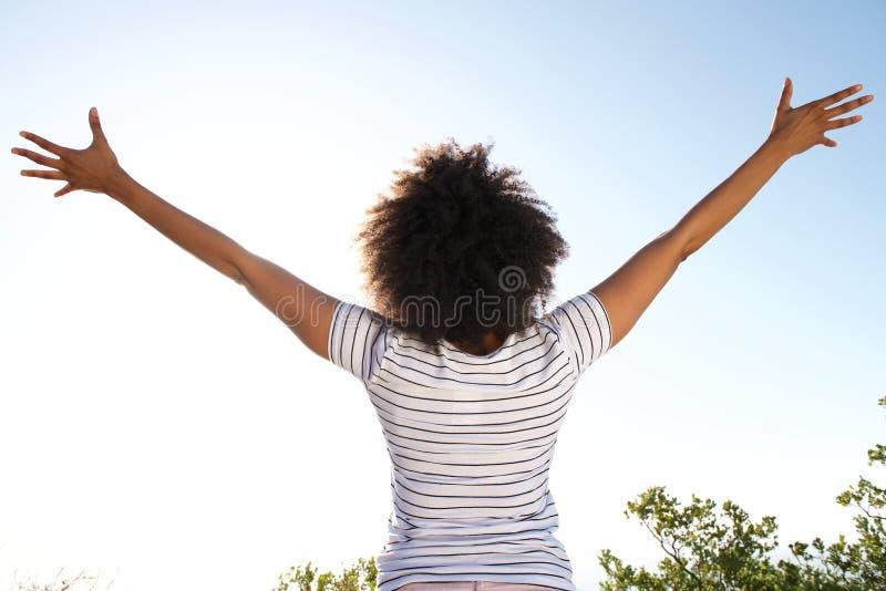 За молодой женщиной смотря солнце при поднятые оружия стоковые изображения rf