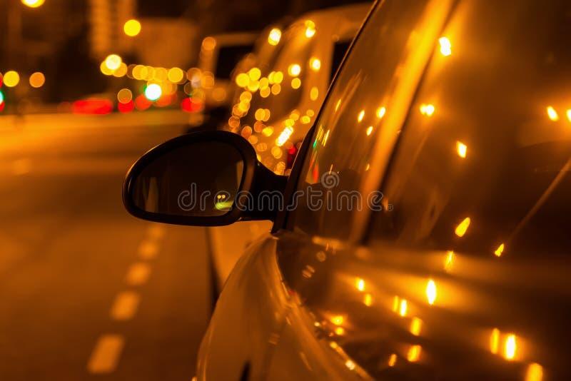 Заднее зеркало автомобиля на ноче стоковые фото