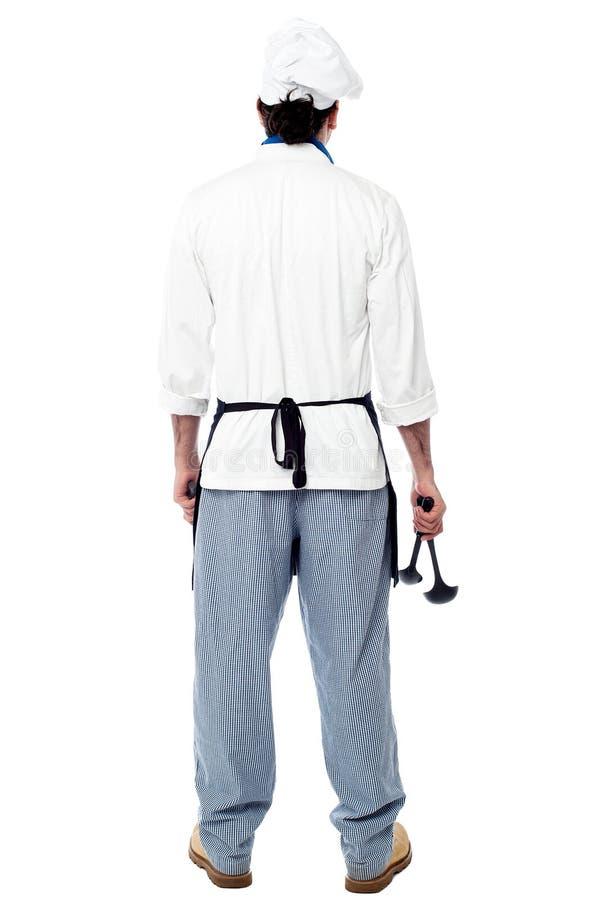 Заднее представление мужского шеф-повара в форме стоковое изображение