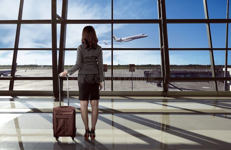 Задний взгляд азиатской женщины носит чемодан в авиапорте стоковые изображения rf