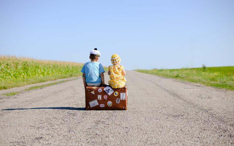 Задний взгляд детей на чемодане сверх стоковые изображения rf