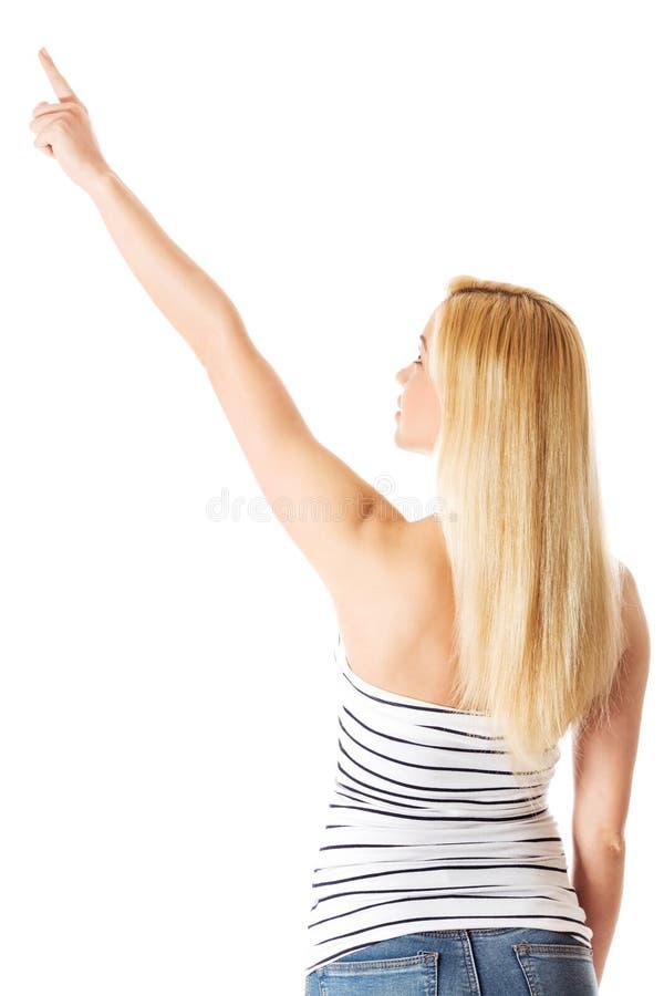 Задний взгляд женщины в указывать на космос экземпляра, на белой предпосылке стоковое фото rf