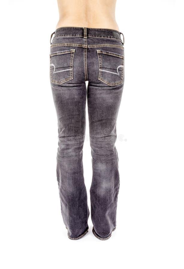 Задний взгляд женщины нося увяданные черные джинсы стоковая фотография