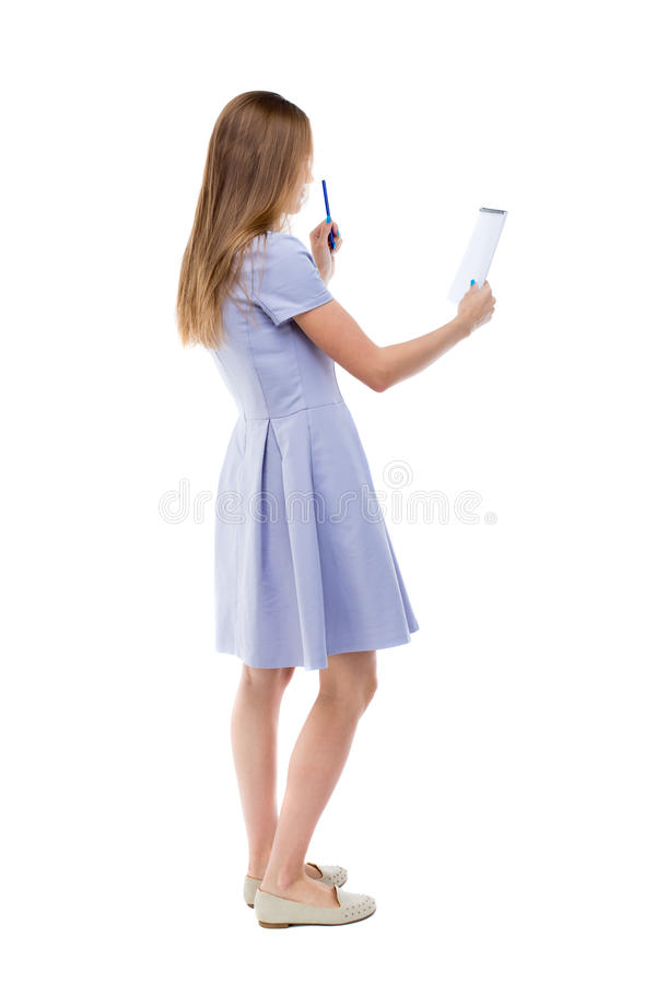 Задний взгляд женщины стоек принимает примечания в тетради стоковое изображение rf