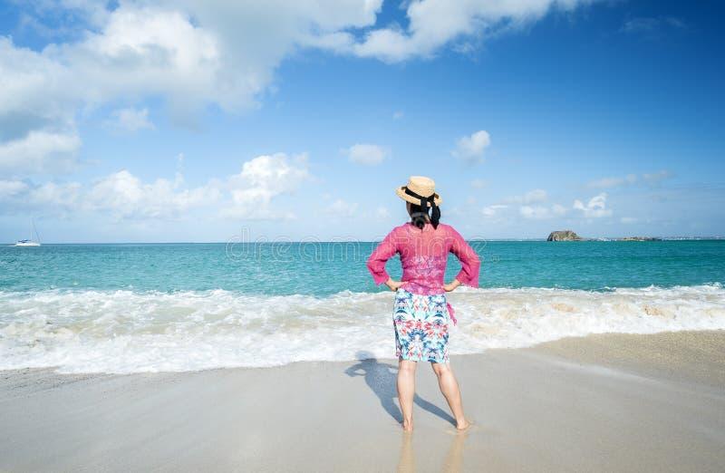 Задний взгляд женщины стоя на пляже 2 стоковое фото