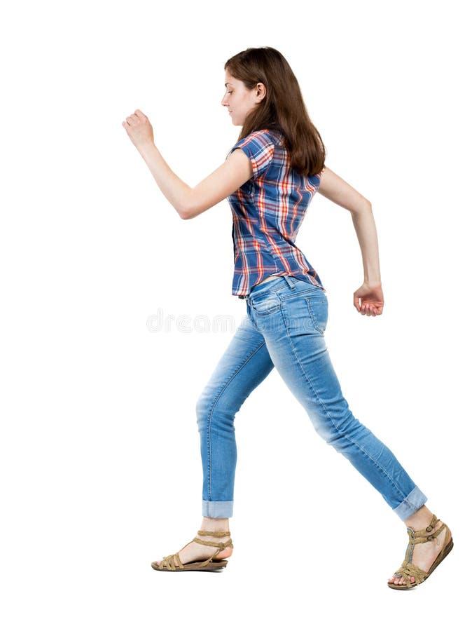 Задний взгляд идущей женщины в джинсыах стоковое фото rf