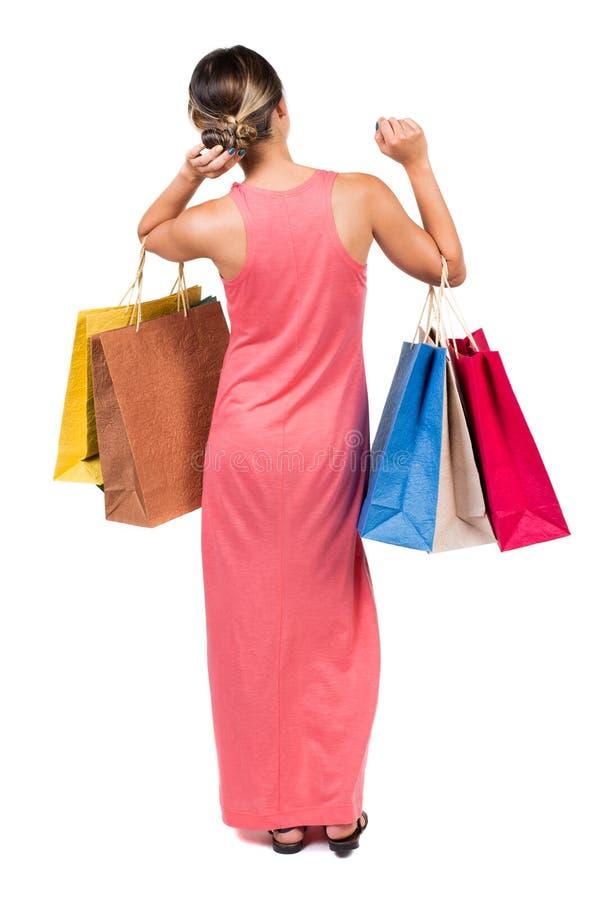 Задний взгляд идя женщины в женщине платья с хозяйственными сумками стоковое изображение