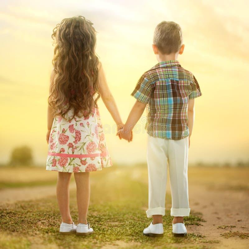 Задний взгляд маленьких ребеят держа руки на заходе солнца стоковые фотографии rf