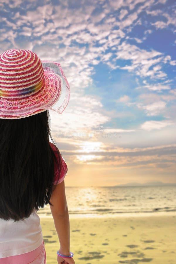 Задний взгляд маленькой девочки смотря к пляжу с голубым небом на s стоковые фото