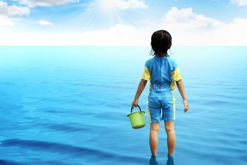 Задний взгляд маленькой девочки смотря океан стоковые изображения rf