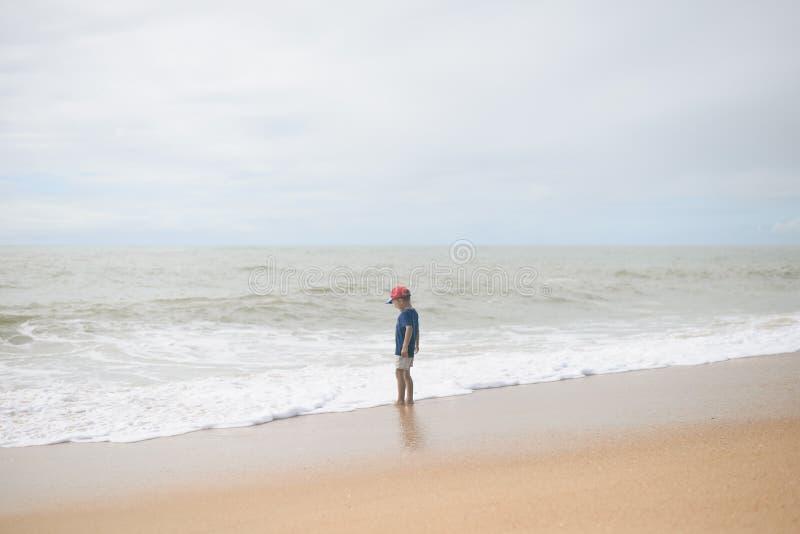 Задний взгляд мальчика идя вдоль пляжа во время захода солнца стоковые изображения rf