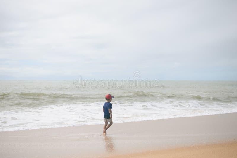 Задний взгляд мальчика идя вдоль пляжа снаружи во время захода солнца стоковые изображения rf