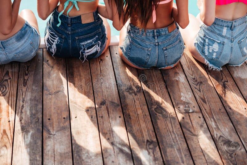 Задний взгляд милых маленьких девочек сидя на бассейне стоковое фото