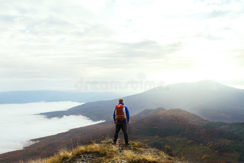 Задний взгляд молодого туристского hiker при рюкзак стоя на верхней части горы и смотря красивый желтый цвет стоковое изображение
