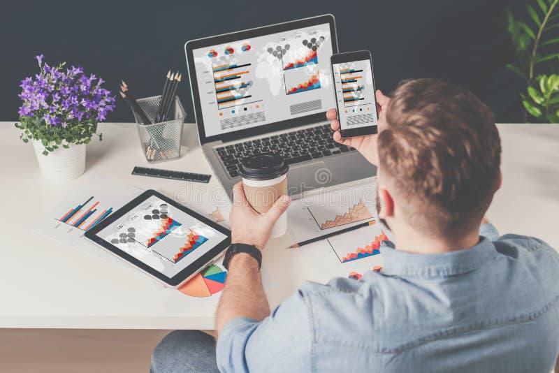 задний взгляд Молодой бородатый бизнесмен в рубашке джинсовой ткани сидит в офисе на таблице и использует smartphone с диаграммам