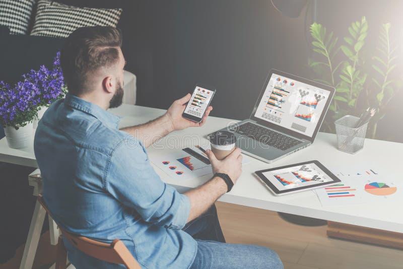 задний взгляд Молодой бородатый бизнесмен в рубашке сидит в офисе на таблице и использует smartphone с диаграммами, диаграммами и стоковые фотографии rf