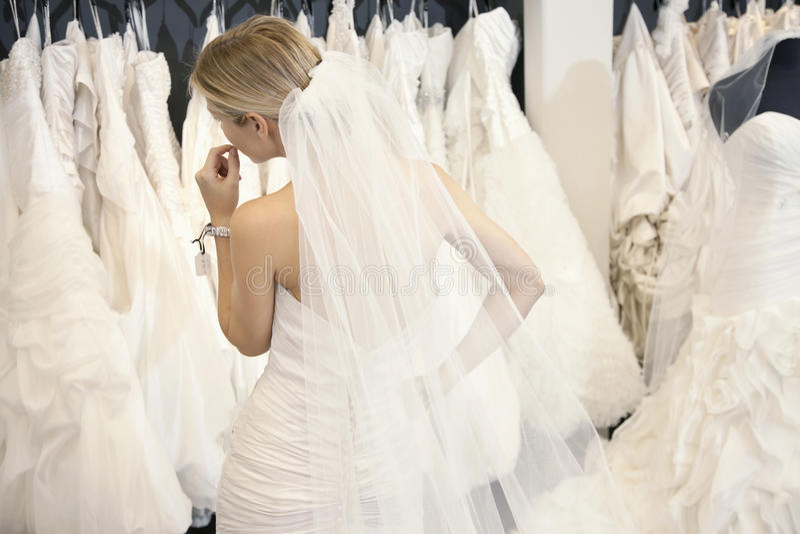 Задний взгляд молодой женщины в платье свадьбы смотря bridal мантии на дисплее в бутике стоковое фото