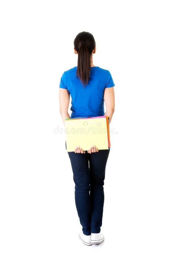 Задний взгляд молодой женщины студента держа тетрадь. стоковые фото