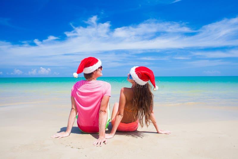 Задний взгляд молодых пар в шляпах santa сидя на стоковые фото