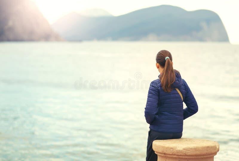 Задний взгляд одной девушки подростка думая самостоятельно и наблюдая море стоковые изображения rf