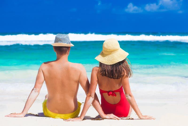 Задний взгляд пар сидя на тропическом пляже в Baie Lazare Mahe, Сейшельские островы стоковые фото