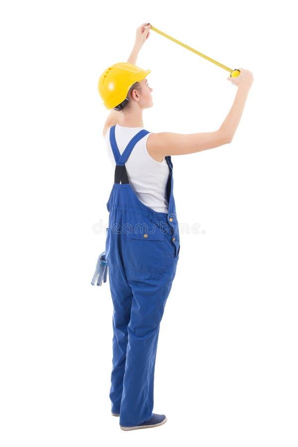 Задний взгляд построителя женщины в workwear измеряя что-то с стоковая фотография rf