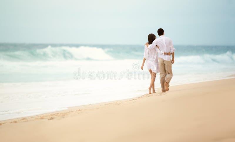 Задний взгляд романтичной пары идя на пляж стоковые фото