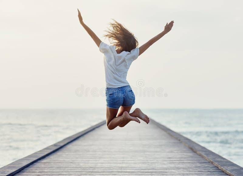 Задний взгляд скача девушки на пристани стоковое фото rf