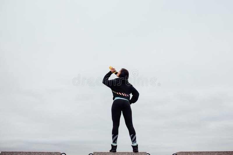 Download Задний взгляд спортсмена с бутылкой, выпивая после работать Стоковое Изображение - изображение насчитывающей lifestyle, небо: 81805687
