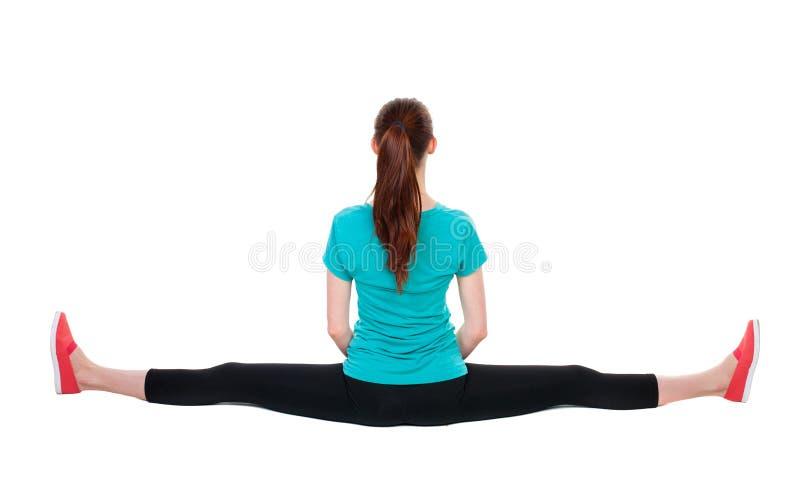 Задний взгляд стоять молодая красивая женщина в платье спорта, который включили в Pilates стоковое фото rf