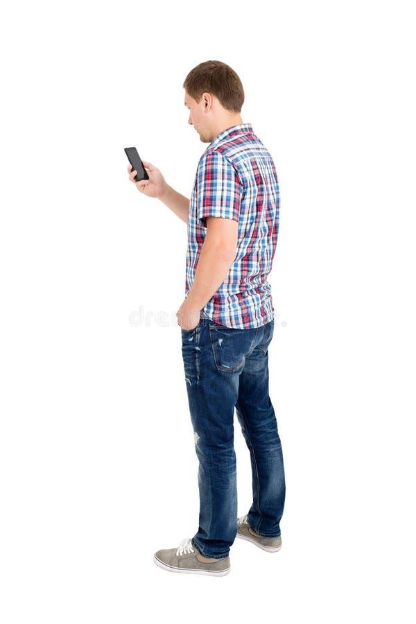 Задний взгляд стоять молодые человеки и использования мобильного телефона стоковая фотография rf