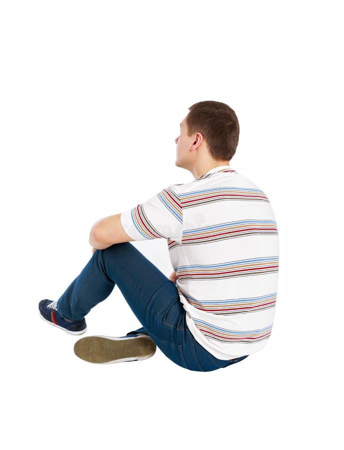 Задний взгляд усаженного красивого человека в футболке и джинсах смотря вверх стоковое изображение