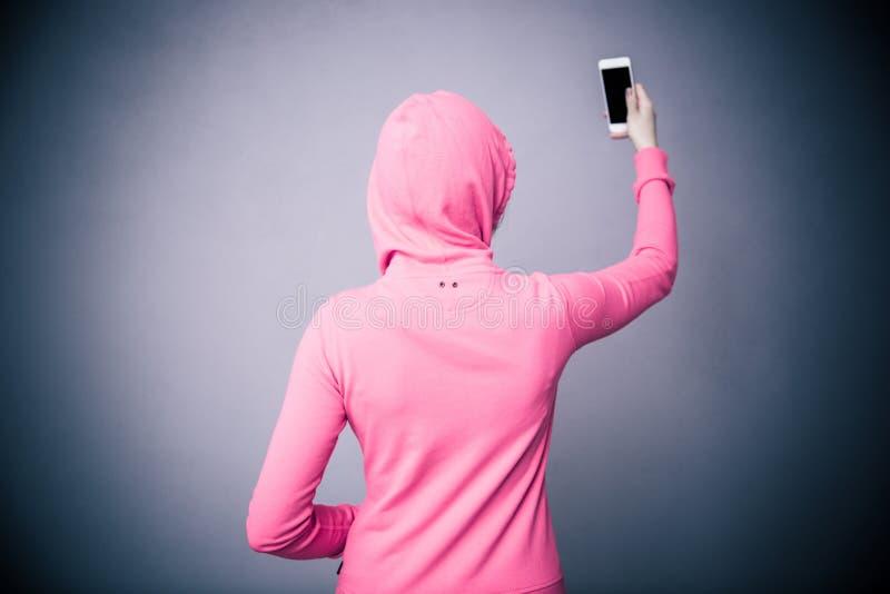 Задний портрет взгляда женщины держа smartphone стоковые фотографии rf
