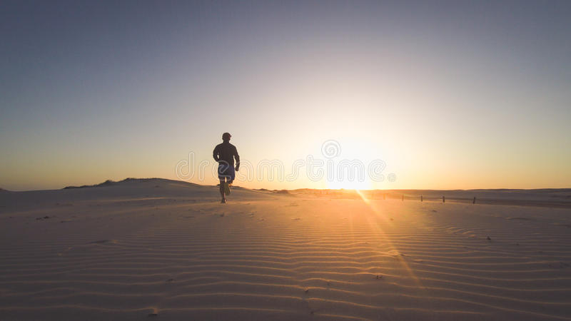 Задний силуэт взгляда человека бегуна бежать вперед на пляже на заходе солнца с солнцем на заднем плане Винтажное изображение сти стоковые изображения rf