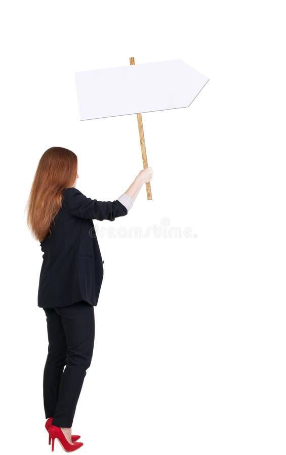 Задняя бизнес-леди взгляда показывая доску знака стоковое фото rf