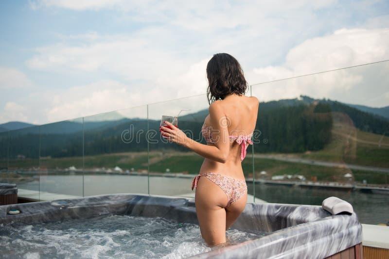 Задняя девушка брюнет взгляда в бикини стоя с коктеилем на джакузи outdoors на каникулах стоковые фотографии rf