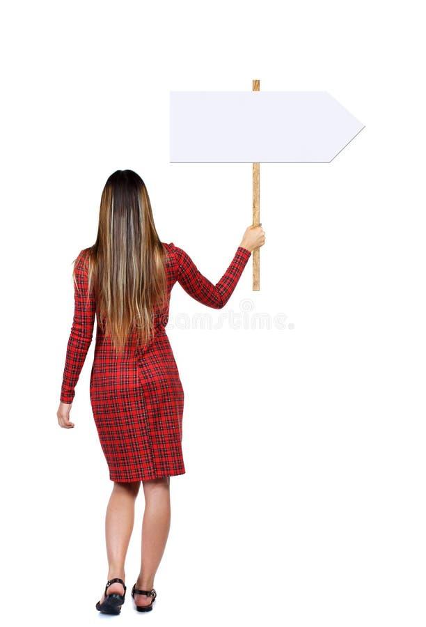 Задняя женщина взгляда показывая доску знака стоковые фото