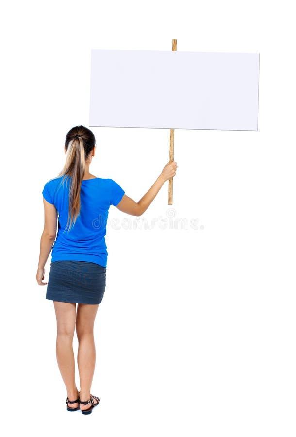 Задняя женщина взгляда показывая доску знака стоковая фотография rf