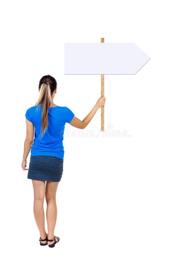 Задняя женщина взгляда показывая доску знака стоковое изображение