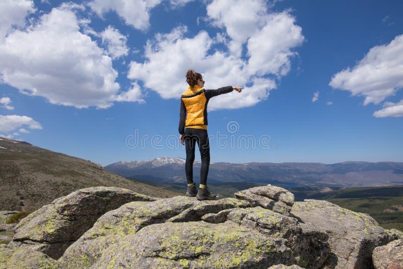 Задняя женщина na górze горы указывая с рукой стоковое изображение rf