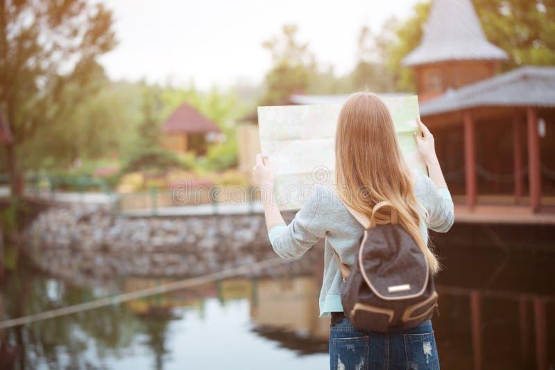 Задняя сторона девушки путешественника ища правильное направление на карте, оранжевом свете захода солнца, путешествуя вдоль Евро стоковое фото