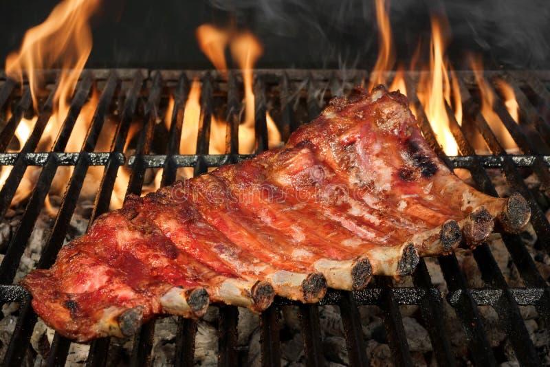 Задняя часть или Spareribs младенца свинины на гриле BBQ с пламенами стоковое фото rf