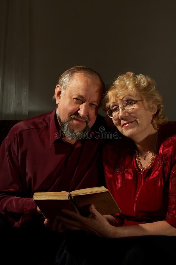 за пожилыми счастливыми супругами чтения стоковое изображение