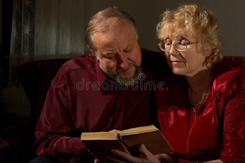 за пожилыми счастливыми супругами чтения стоковое фото