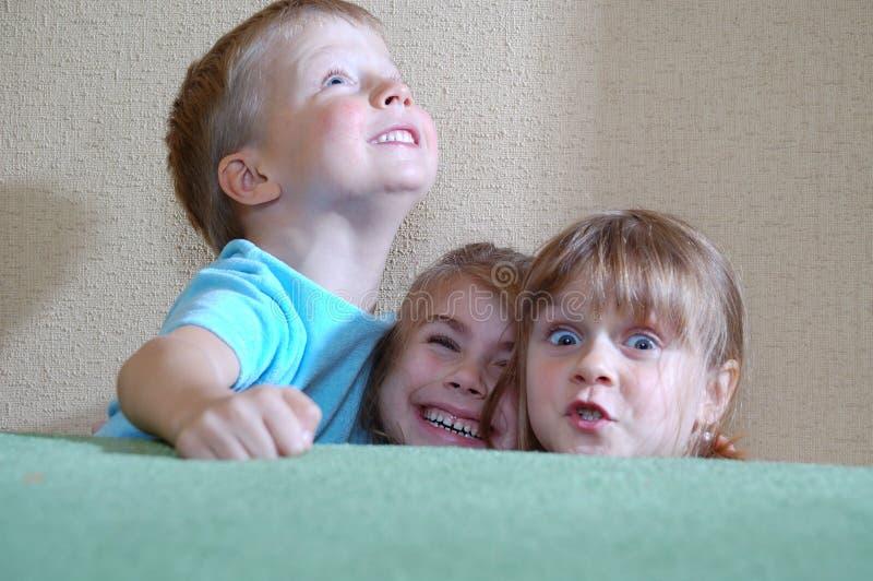 за софой детей счастливой пряча стоковая фотография