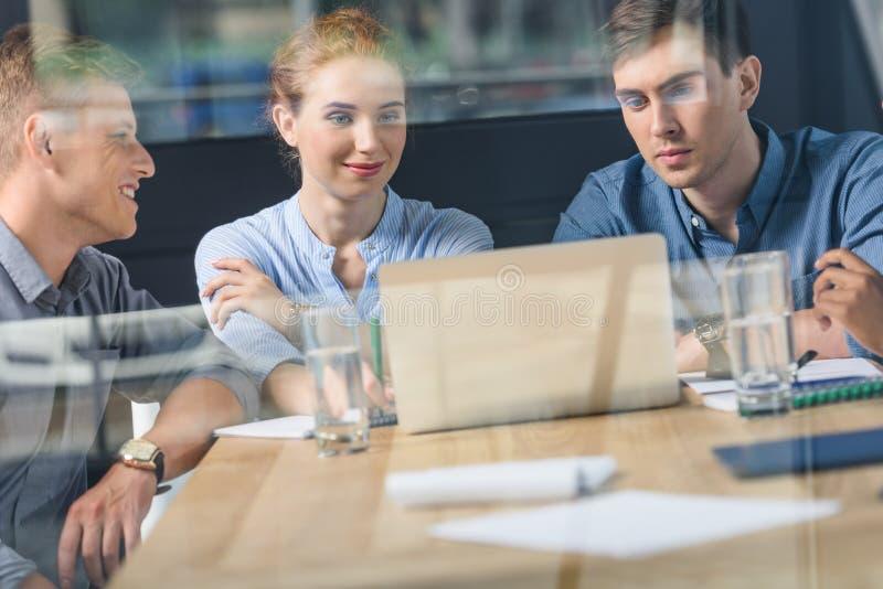 За стеклянным взглядом молодой команды обсуждая проект в современном стоковое изображение