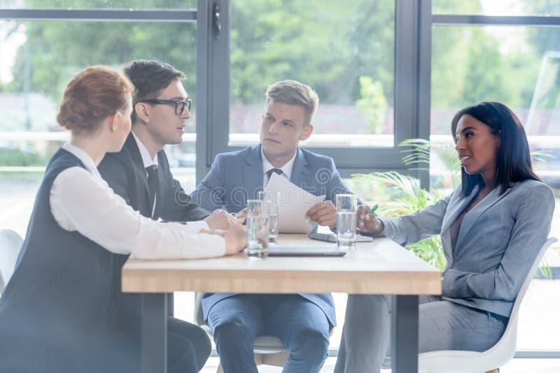 За стеклянным взглядом сконцентрированных бизнесменов обсуждая проект в современном стоковая фотография