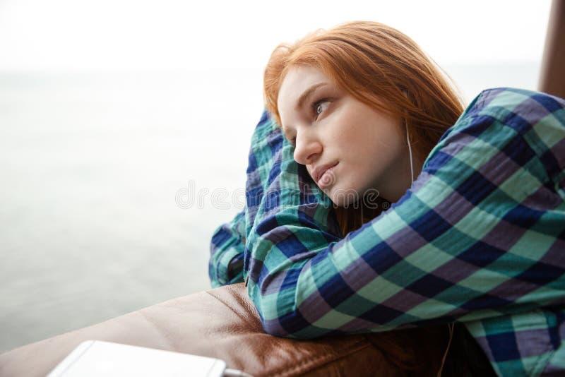 Задумчивая дама слушая к музыке и смотря прочь стоковые фотографии rf