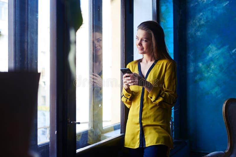 Задумчивая девушка используя мобильный телефон пока полагающся на окне стоковое фото rf